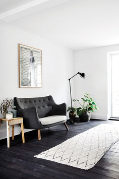 This stylish apartment in Copenhagen, Denmark uses predominately black and white on the ground floor, with white walls, black stained wood flooring and black industrial style kitchen island and cabine