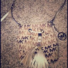 Michael Kors cross body purse Super cute cross body Michael Kors purse, 2 pockets on the inside and one on outside. The tassels are just adorable. The strap is also adjustable! Michael Kors Bags Crossbody Bags
