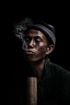 A man smokes in Bac Ha market in Vietnam