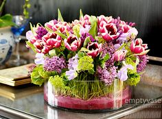 """The Charmer!  Description:A gorgeous mix of Dutch Tulips, Lilacs, Viburnum, and sweet peas complimented with grass and all masterfully arranged in a 10"""" x 4"""" low glass cylinder filled with pink and red sand. This arrangement is approx. 16"""" tall."""