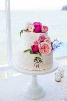 Two tier textured fuchsia ranunculus topped wedding cake: http://www.stylemepretty.com/california-weddings/san-francisco/2017/01/03/classic-san-francisco-stunner/ Photography: Janae Shields - http://janaeshields.com/