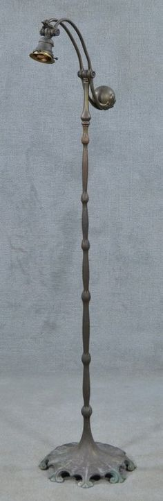"""Early 20th century. Electric bronze counter-weight lamp with """"S"""" arm. Lamp shaft or """"stem"""" having segmented lily blossom motif. Scalloped Art Nouveau base with eight scrolled feet. Shade no longer present. With evidence of polychrome patination. Base with grime and verdigris. Signed """"Tiffany Studios 619."""""""