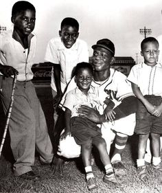 photo of Satchel Paige posing with the children of photographer Ernest Withers from about 1953
