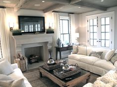 2 cream sofas with chairs and fireplace in front