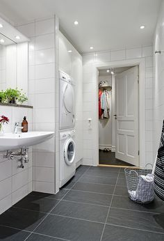 laundry in bathroom, dividing wall, wall mounted sink with built out wall behind it W/D fixtures behind?
