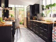 a bright and sunny kitchen with dark wood