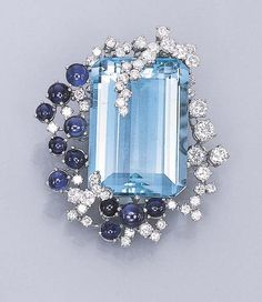 I really like this setting... AN AQUAMARINE, SAPPHIRE AND DIAMOND CLIP BROOCH   Set with a rectangular-cut aquamarine, held by overlapping circular-cut diamonds, to the circular-cut diamond and cabochon sapphire surround, mounted in 18k white gold