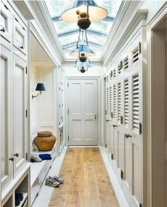 A door from the garage leads to a long, hallway mudroom... A built-in bench with shelves, louvered lockers, other additional storage, along with the lighting, makes this a great mudroom.