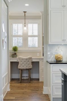 Long kitchen pantry features a built-in desk, placed below windows dressed in plantation shutters, paired with a beige tufted stool atop rustic wood floors.