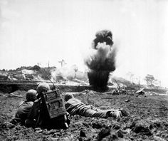 A 6th Marine Division demolition crew watches explosive charges detonate and destroy a Japanese cave on Okinawa May 1945.