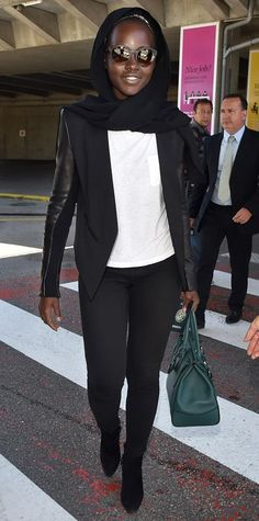 Lupita Nyong'o arrived at Nice Airport in France in a sleek ensemble that consisted of a white T-shirt and a blazer, leggings, and boots—all in black. She topped off the look with gray sunglasses, a green handbag, and a black scarf draped around her head.