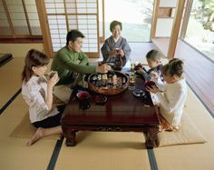 This is a Japanese family eating. They wait for there father to eat with them. They sit on the floor  to eat.