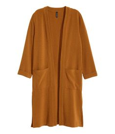 Coat in a textured weave with front pockets, 3/4-length sleeves with sewn-in turn-ups, a vent at the back and no buttons. Unlined.