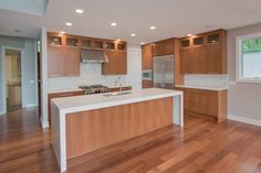 Kitchen: hardwood floors, granite waterfall counters, matching granite backsplash, stained cabinets, stainless steel appliances