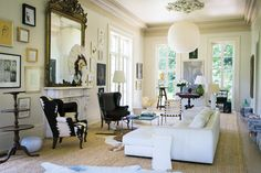 """In the Garden District of New Orleans, the photographer Paul Costello and his wife, Sara Ruffin Costello, live in a storied pink house that was what Paul calls """"a chic disaster"""" when they found it in 2010. Here, their family room with a white leather couch from Design Within Reach, vintage wing chairs, Noguchi paper lanterns and a mirror original to the house above the fireplace. (Photo: Paul Costello)"""