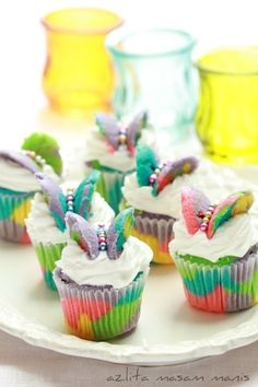 cut tops off of tie dye cupcakes, cut in half, ice with white icing, place cupcake top in shape of butterfly, use candy to make butterfly torso. Could use greenTwizzlers or fruit roll-ups for antenna.