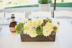 Flowers in a wooden box. Nice low arrangement.  Not sure of the green succulents in the design though.