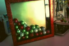 Simply get any shadow box and decorate it with jingle balls and paint the frame any color for a christmas frame!!!!