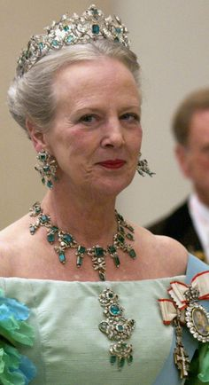 Danish Queen Margrethe wearing an Emerald Parure (part of the Crown Jewels). In total: 67 emeralds and 2,650 diamonds composing a parure of a tiara, necklace, earrings, and brooch. The brooch itself can disassemble into three smaller brooches, and can also serve as a pendant for the necklace.