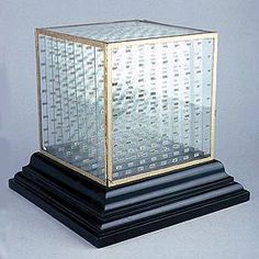 Frost's cube of nine, Whipple Museum of the History of Science, Cambridge.  Length 289mm; breadth 286mm; height 270mm. Turned square ebony base carries glass cube (edges covered with gold paper) which contains 7 glass plates. Each plate, together with the back and front of the cube carries 81 numbers, printed on paper, arranged in 9 rows of 9 columns.  Each position on the grid has two numbers, one facing in each direction.  These numbers run from 1 to 729.