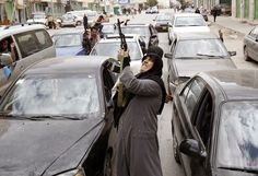 A woman rebel fighter supporter fires an AK-47 rifle as she reacts to the news of the withdrawal of Libyan leader Muammar Gaddafi's forces from Benghazi on March 19.