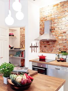 Cozy little kitchen with exposed brick wall and cute pantry