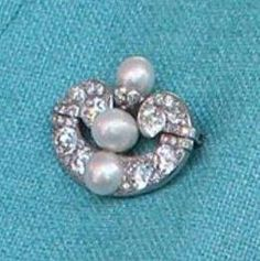 Greville Scroll Brooch. Scroll of diamonds around 3 pearls, set in platinum. These are the jewels of Mrs. Ronald Greville, left to the Queen Mother in 1942, made by Cartier using some of her own stones in 1929. The third pearl is actually a drop pearl, but it seems to be worn with the drop on top mostly. The brooch passed to the Queen after the Queen Mother's death in 2002.