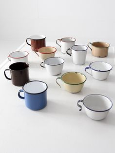 A collection of twelve enamelware mugs. Each mug is different adding to the whole. The style of these mugs have been used in kitchens for over 100 years, and make great outdoor and camp utensils. - en