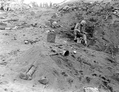 A dead Japanese soldier buried under a mound of earth on Iwo Jima/February 1945