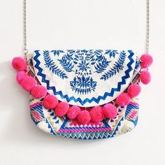 This pom pom purse with bright blue, pink and white accents in colorful embroidery is this season's most chic accessory. The shoulder bag features a detachable chain link cross body strap and a magnet