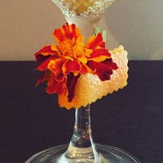 Piel de cítrico sujetándolo con una mini pinza en el tallo de la copa, colocamos una flor y listo. Espero que os haya gustado