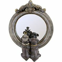 "Round wood wall mirror with a fleur-de-lis scroll top and artful dog accents.       Product: Mirror decor    Construction Material: Wood and mirrored glass  Color: Distressed gray frame  Features: Fleur-de-lis scroll topDog accentsDimensions: 10"" H x 8"" W x 3.5"" D"