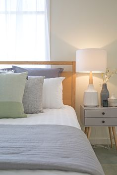 master bedroom, mint cushion, grey throw, timber queen bed frame, white sheer curtains