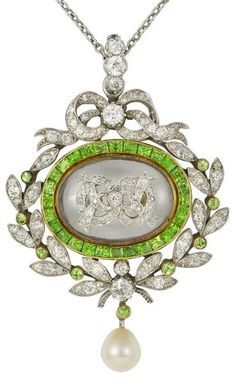 A turn of the century green demantoid garnet and diamond pendant, the rock crystal center with applied diamond motif surrounded by calibré-cut demantoid garnets, within a diamond and demantoid laurel wreath and bow, circa 1900.
