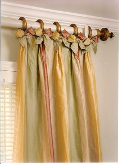 Silk drapes on rings with interesting bows and finial on a white rod