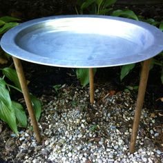 Found the idea online- DIY bird bath: stained dowel rods in the ground with a serving platter set on top.
