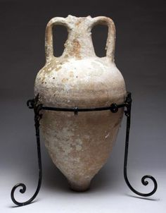 Greek Hellenistic Transport Amphora Dressel. Late Hellenistic Transport Amphora, ca. 100 BCE. Dressel amphora, fine, rare torpedo-shaped terracotta vessel with long cylindrical neck with two elegant side handles, and pointed base. Such amphorae were used throughout antiquity to transport wine, oil, and other precious liquid across the Mediterranean. Beautiful and interesting encrustation throughout. This and other rare ancient Greek art on offer at CuratorsEye.com