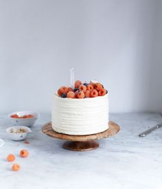Berry-topped cake on a hand-carved wooden cake pedestal from Herriott Grace