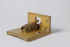 Marshall | Model  van een kanon van 30 pond in batterij, Marshall, Anonymous, 1827 | Model van een kanon van 30 pond op Marshall-affuit op een scheepsdeel met deel van de scheepswand, incompleet. De houten loop, lang 22,5-23 cm, is niet uitgeboord; het heeft een platte druif met broekingring. De affuit bestaat uit twee delen. Het voorste stuk zit met een spilbout in zware messing beugels aan de poortdrempel vast; het is een zwaar houten blok met een dwarse roller eronder voor het baksen en…