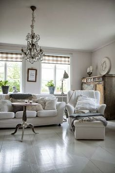 Love the juxtaposing idea of the casual plaid Roman shades and the fancy chandy.