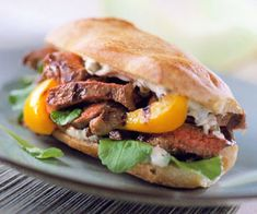 The classic French mayonnaise-based sauce called remoulade adds a hint of rustic sophistication to this steak sandwich perked up by peppery arugula and grilled sweet peppers./