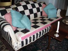 Black white and pink painted sofa with checks, polka dots, and stripes.