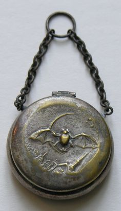 Victorian Bat and Quarter Moon Chatelaine Piece  This fun Victorian chatelaine piece features a bat flying over a town with a quarter moon in the background.  The chatelaine piece could have functioned to hold rouge or coins