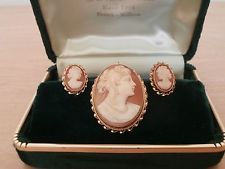 Cameo Jewelry Set... Women's jewelry, 1 brooch and 1 set of earrings, from Japan, circa early 1950s, pink background, white face with woman facing to the right, gold detail