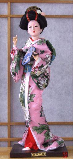 Geisha doll in pink green kimono with fan