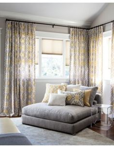 Curtain rods are placed high above the window to create height.  Notice that the ceiling is straight along one wall and vaulted on the other.
