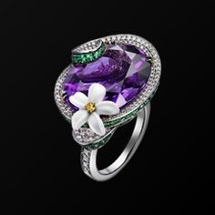 Limelight Blue Moon cocktail inspiration ring in 18K white gold set with one oval-cut amethyst (approx. 25 ct), 100 round emeralds (approx. 1.49 ct), 296 brilliant-cut diamonds (approx. 1.46 ct), one round yellow sapphire (approx. 0.30 ct), and sculpted white chalcedony.