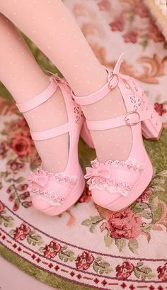 An adorable design high heeled shoe with corset tie heels in baby pink. The toe is decorated in lace and lace effect leather and a bow sits neatly in the centre. Has top and ankle straps with matching gold clasps. Beautifully lined in a posy print. The shoes have raised wedge toe to give more height.