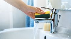 Closeup of unrecognizable person cleaning bathroom tap and sink with a sponge. The tap is shiny disinfected.