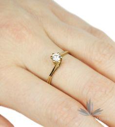 Klasyczny pierścionek wykonany ze złota próby 333. W wyrobie osadzono Cyrkonię w centralnym punkcie o średnicy około 0,5 cm o szlifie brylantowym. Delikatna oprawa koszyczkowa. Wzór z powodzeniem nadaje się na pierścionek zaręczynowy.